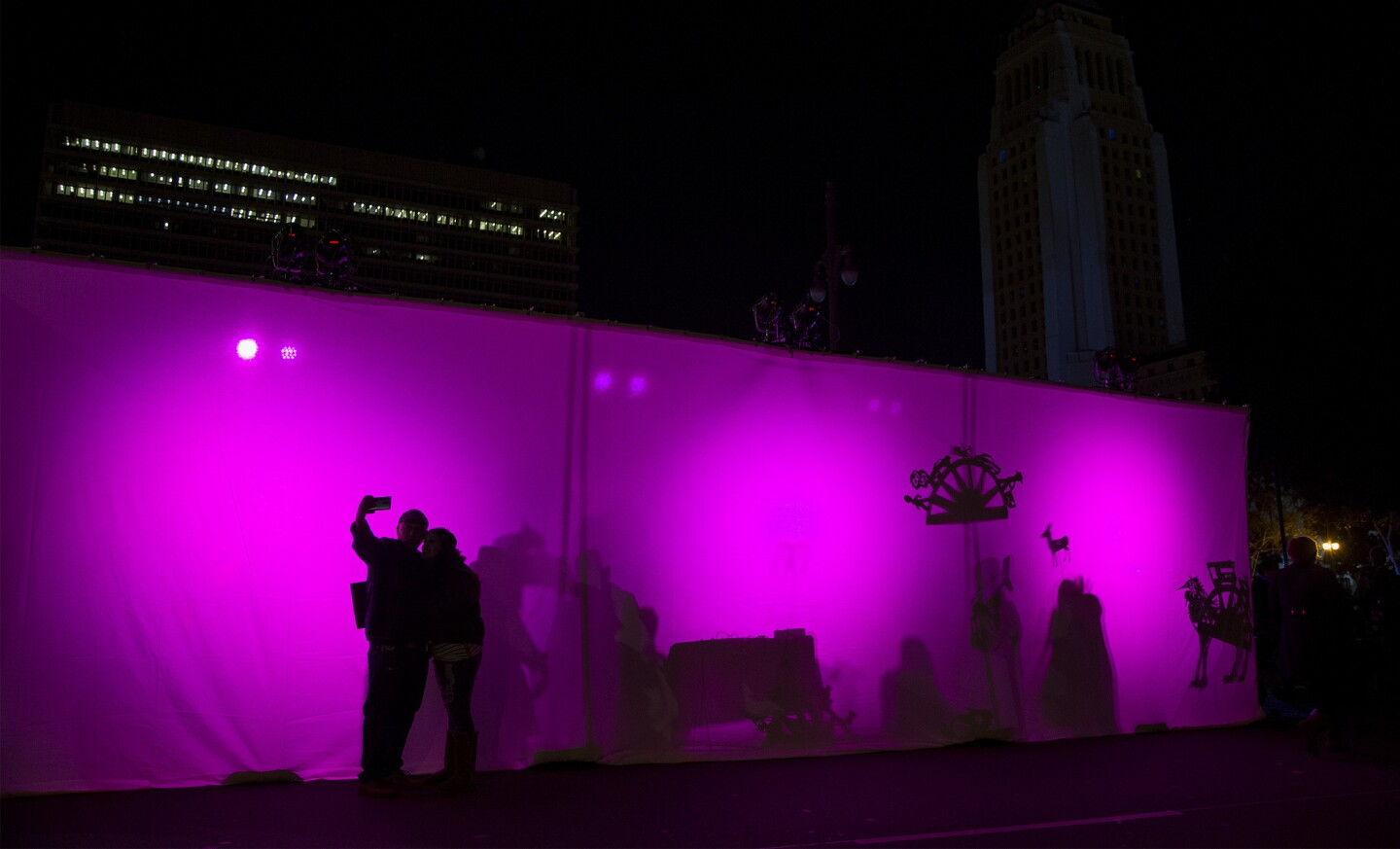 A couple pose for a selfie outside a puppet booth during the New Year's Eve celebration at Grand Park in Los Angeles.