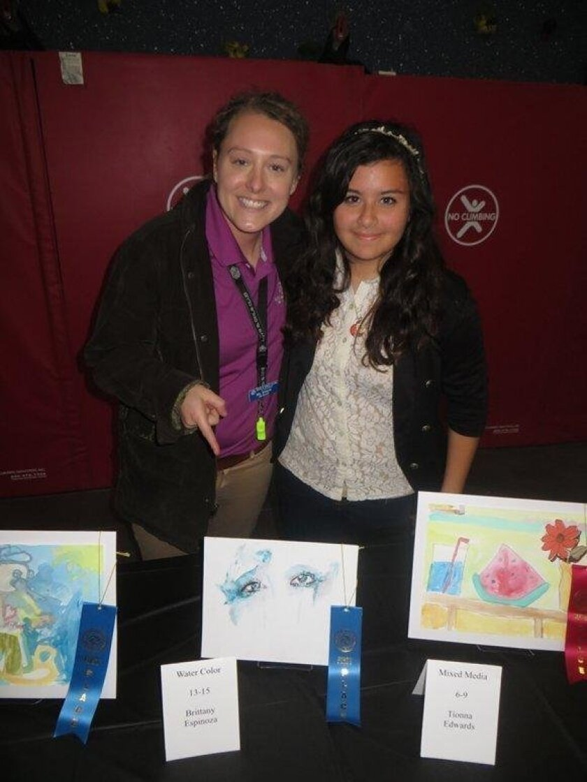 Boys & Girls Club of Oceanside member Brittany Espinoza (right) stands behind her first-place watercolor. Next to her is her mentor Shayla Ragone.