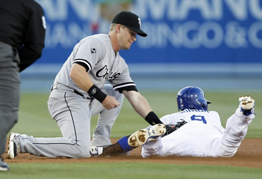 Chicago White Sox second baseman Gordon Beckham, left, tags out Los Angeles Dodgers' Dee Gordon, right, on a steal attempt in the first inning of a baseball game on Wednesday, June 4, 2014 in Los Angeles. (AP Photo/Alex Gallardo)