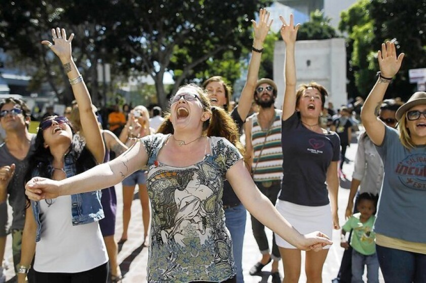 Lauren Rock of Los Angeles dances with dozens of other demonstrators as a band called the Mowglis performs on the steps of City Hall for people participating in Occupy L.A.