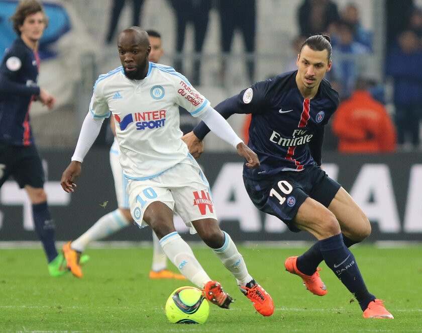 Marseille's Lassana Diarra, left,  challenges for the ball with Paris Saint Germain's Zlatan Ibrahimovic , during the League One soccer match between Marseille and Paris Saint-Germain, at the Velodrome Stadium, in Marseille, southern France, Sunday, Feb. 7, 2016. (AP Photo/Claude Paris)