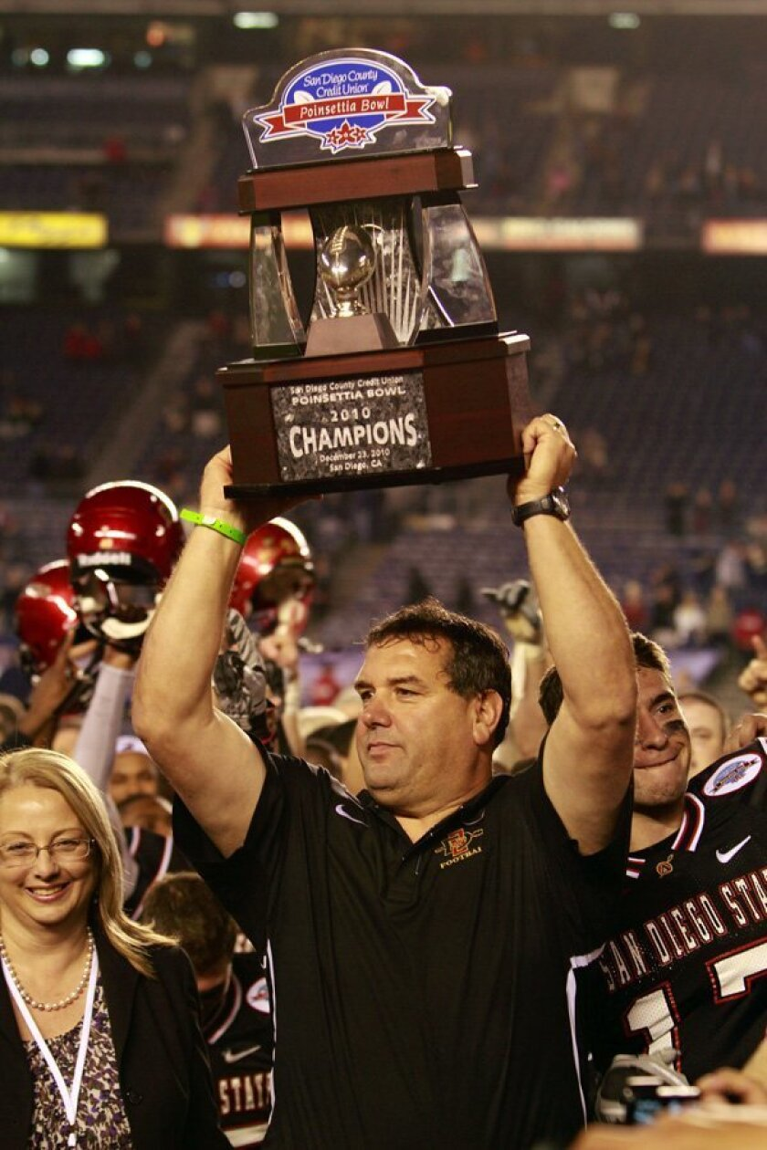 SDSU coach Brady Hoke holds up the championship trophy after the Aztecs beat Navy .