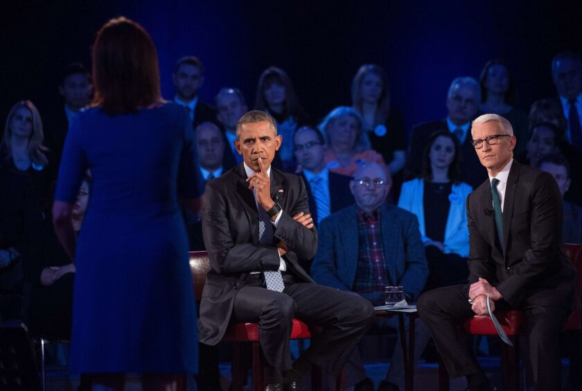 President Obama takes a question at a town hall meeting at George Mason University in Fairfax, Va., on reducing gun violence, as CNN's Anderson Cooper looks on.