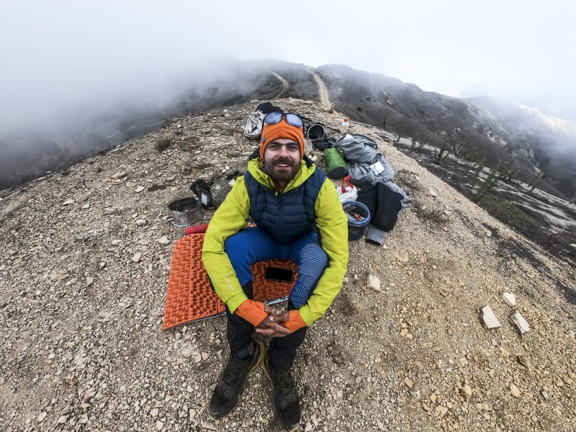 A young man sits on a hilltop surrounded by hiking and camping equipment.