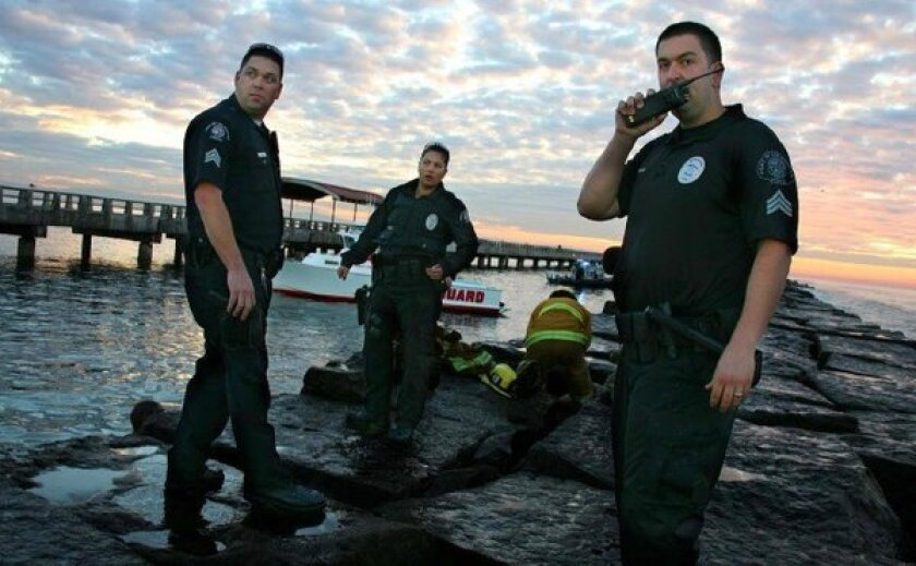 Police and emergency officials stand on a Cabrillo Beach breakwater after a man drowned while trying to rescue two people who had been knocked into the water by a wave.