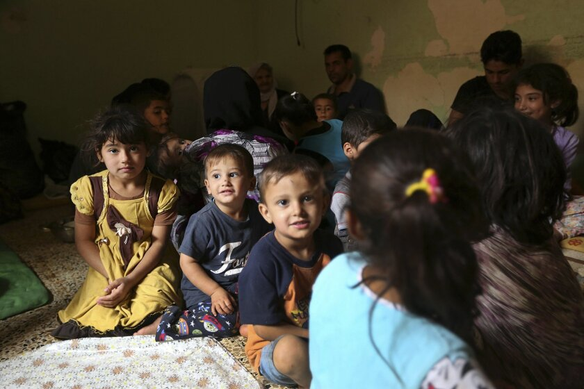 Internally displaced Iraqi Yazidis who fled from Sinjar and other towns after advances by Islamic militants take shelter at a school in Dahuk, 260 miles (420 kilometers) northwest of Baghdad, Thursday, Oct. 2, 2014. The Yazidis now living in the Kurdish city of Dahuk are cautiously optimistic - wary after having already lost so much, but hopeful to return home and pick up the pieces, as the Kurdish military says it is now on a push toward Sinjar, located in the deserts of northwestern Iraq near the Syrian border, in an assault aimed at retaking the town from the extremists. (AP Photo/Hadi Mizban)