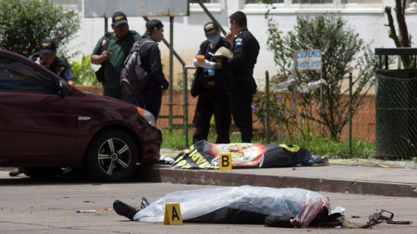 Two bodies, one identified as prison guard Juan Sical Toj, lie covered outside the Roosevelt Hospita