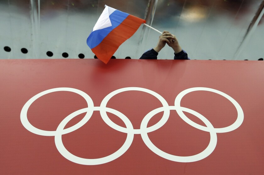 A Russian flag is held above the Olympic Rings at Adler Arena Skating Center during the Winter Olympics in Sochi, Russia.