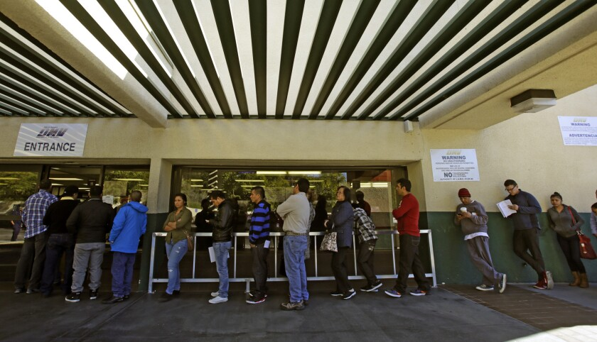 People stand at a DMV office in Los Angeles in 2014. Wait times could grow longer this year as the agency struggles to issue new Real IDs to millions of Californians.