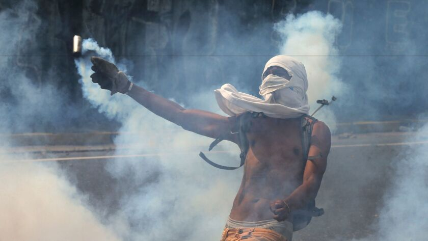 A demonstrator returns a canister of tear gas towards security forces during anti-government protest