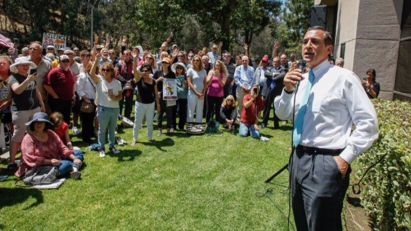 Rep. Darrell Issa (R-Vista) speaks to a crowd of protesters outside his district office.
