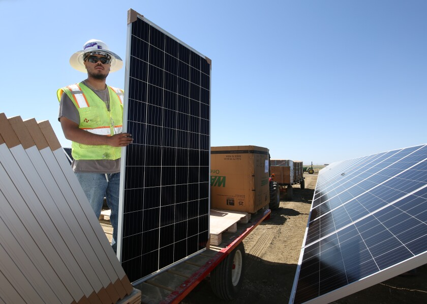 Ricky Figueroa places photovoltaic panels at the construction site of Westlands Solar Park on June 24, 2021.
