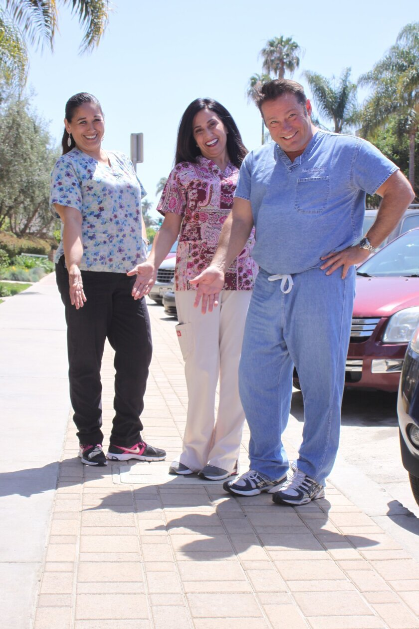 Julie Ramirez, Mary Jane Nunes and Dr. Robert Sunstein stand on what once was grass, but replaced with pavement to save water.