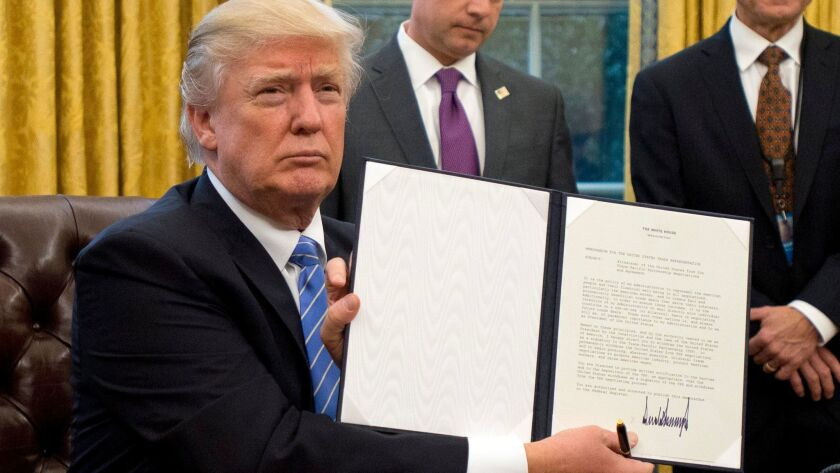 President Trump shows the Executive Order withdrawing the U.S. from the Trans-Pacific Partnership (TPP) after signing it in the Oval Office of the White House on Jan. 23.