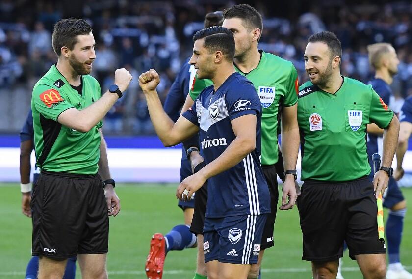 Les joueurs et les officiels frappent au poing plutôt que de se serrer la main avant un match de ligue de football australienne le 7 mars.