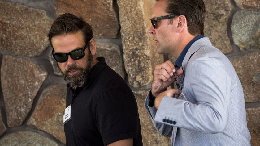 Lachlan Murdoch, left, executive co-chairman of News Corp and 21st Century Fox, walks with brother James Murdoch, chief executive officer of 21st Century Fox, as they attend the annual Allen & Company Sun Valley Conference.