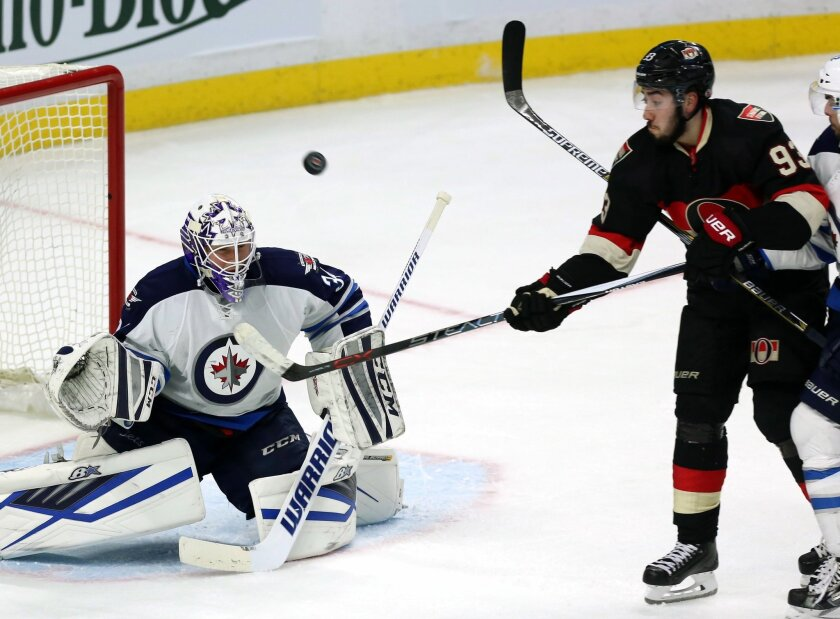 Ottawa Senators' Mika Zibanejad (93) attempts to control a flying puck as Winnipeg Jets goaltender Micheal Hutchinson (34) watches during the first period of an NHL hockey game Thursday, Nov. 5, 2015, in Ottawa, Ontario. (Fred Chartrand/The Canadian Press via AP)