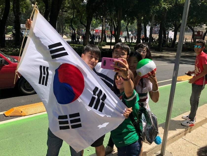 Korean and Mexican fans celebrate despite Mexico's loss to Sweden in the World Cup because South Korean secured Mexico's advancement with its victory over Germany.