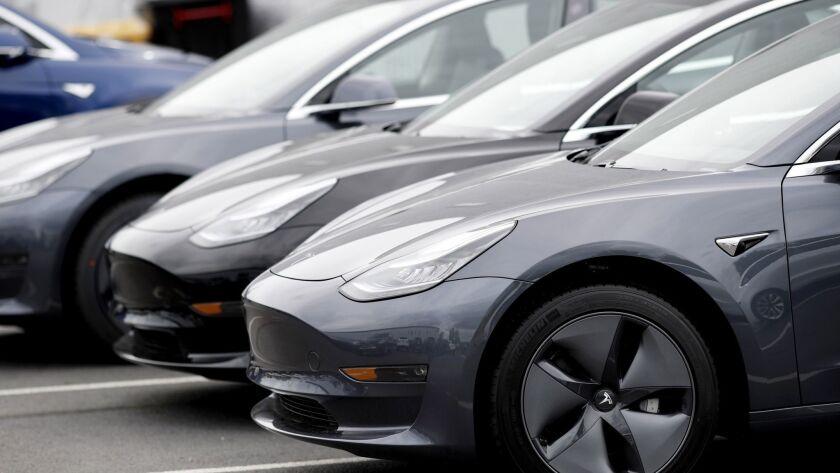 Model 3 sedans sit at a Tesla dealership in Littleton, Colo.