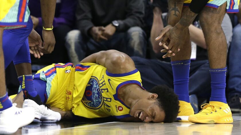 Warriors guard Patrick McCaw lays on the court in pain after falling hard to the court late in the third quarter Saturday.