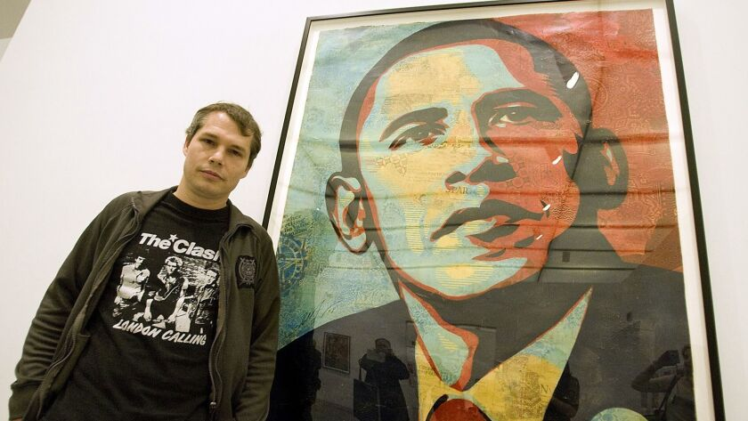 """Artist Shepard Fairey poses beside his """"Obama HOPE"""" image, part of an exhibit of his work at the Ins"""
