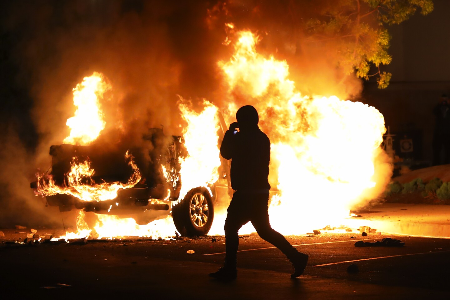 Protestors walk past a fully engulfed vehicle parked on Allison Avenue on fire Saturday night.