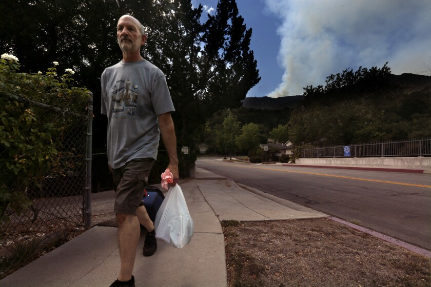 Gregory Lasavio evacuates the Glenwood Oaks community as the La Tuna fire rages in the Verdugo Mountains.