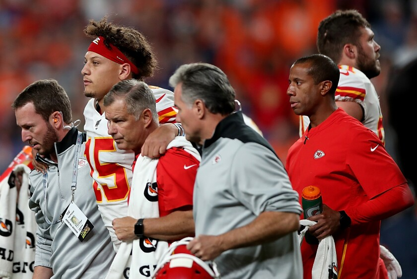 Kansas City Chiefs quarterback Patrick Mahomes is escorted off the field after sustaining a knee injury during the first half against the Broncos.