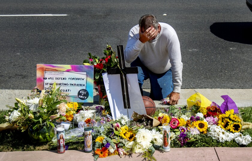 A man kneels at a memorial for Kurt Andras Reinhold