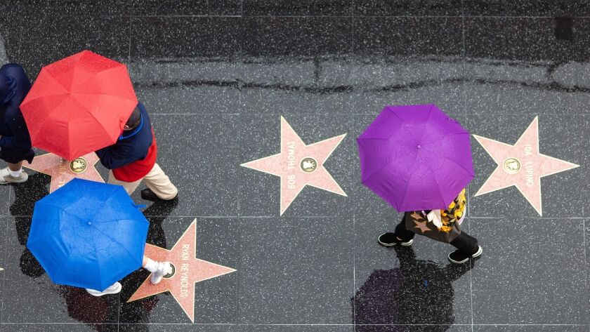 Shielding themselves from the rain, people walk along Hollywood Boulevard on Saturday morning.