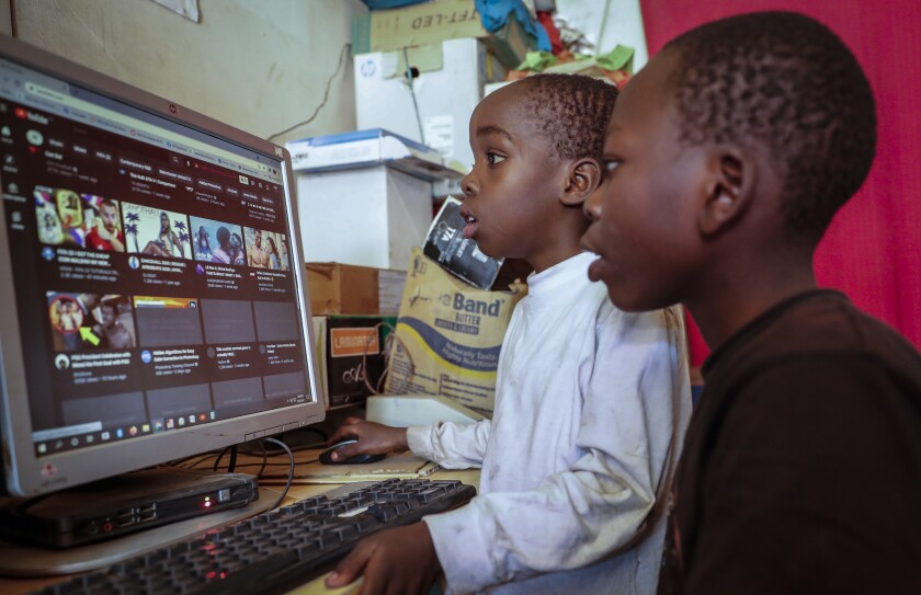 Two young boys use a computer at an internet cafe in the low-income Kibera neighborhood of Nairobi, Kenya Wednesday, Sept. 29, 2021. Instead of serving Africa's internet development, millions of internet addresses reserved for Africa have been waylaid, some fraudulently, including in insider machinations linked to a former top employee of the nonprofit that assigns the continent's addresses. (AP Photo/Brian Inganga)