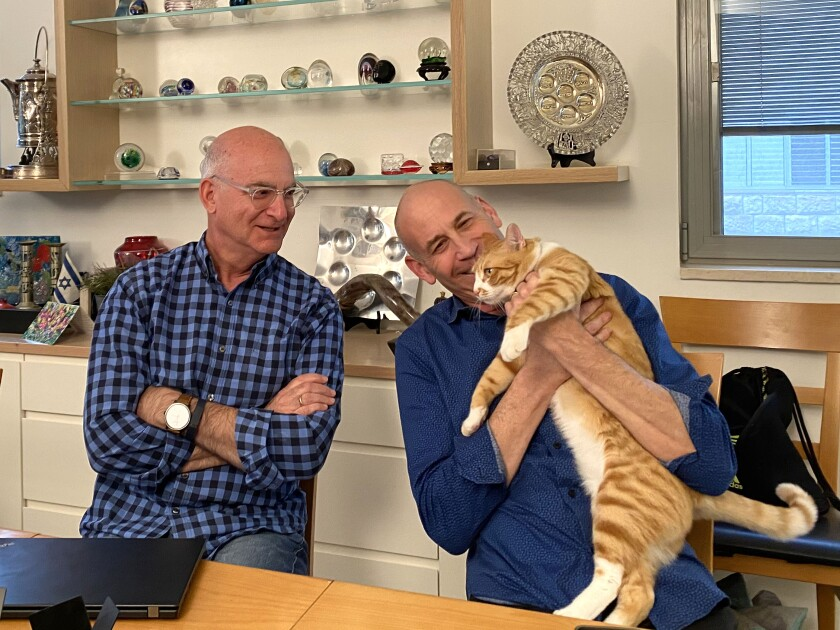 Rabbi Donald Goor, left, and Cantor Evan Kent, in their Jerusalem living room, with their rescue cat, Archie.