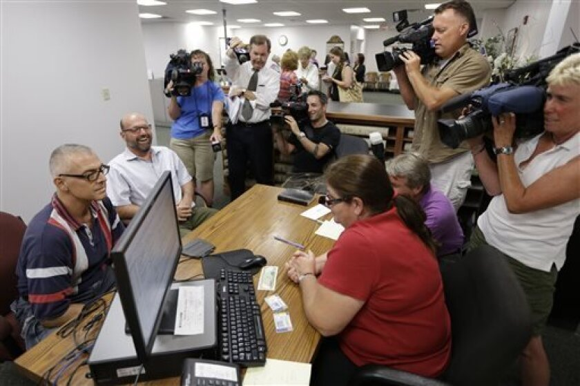 FILE - In this Wednesday, July 24, 2013 file photo, Marcus Saitschenko, left, and James Goldstein obtain a marriage license at a Montgomery County office in Norristown, Pa. For two months, an elected court clerk in the Philadelphia suburbs has been giving something to same-sex couples they have not been able to get anywhere else: a Pennsylvania marriage license. Now a court has to decide whether the clerk has singlehandedly added Pennsylvania to the growing list of states that formally sanction