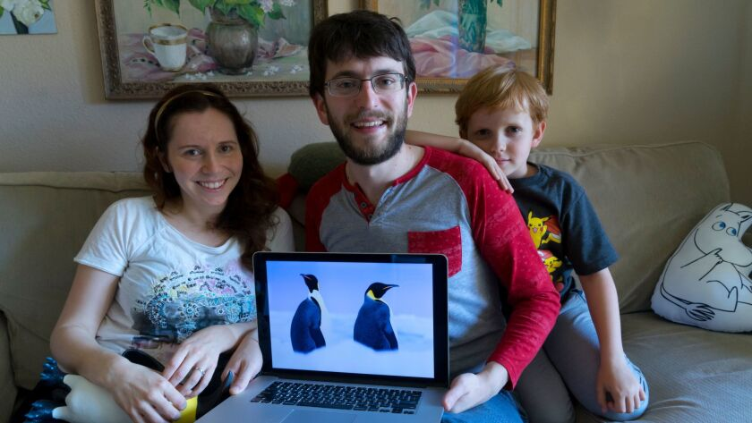 Alex Myers, center, shows off a photograph of penguins taken in Antarctica by his wife, Daria, left, when they traveled there with their son Nikolai, right, in January.