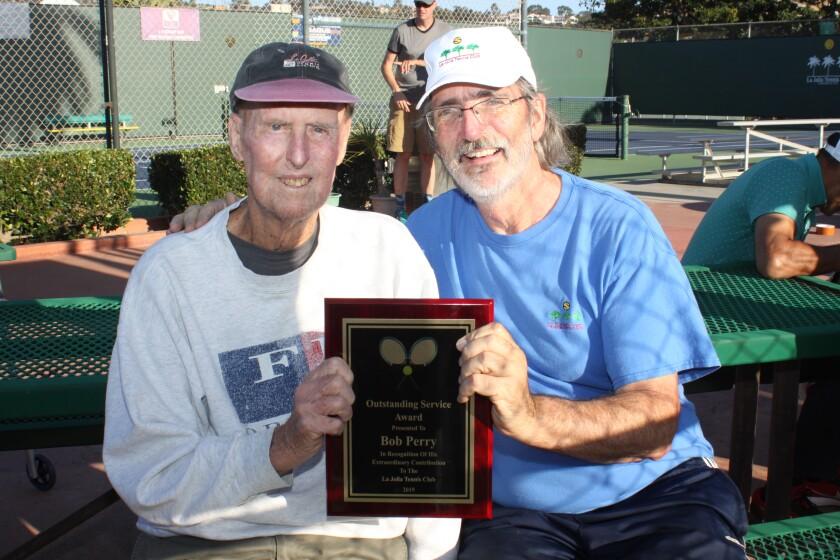 Former La Jolla Tennis Club director Bob Perry (left) receives a plaque from current Club manager Scott Farr.
