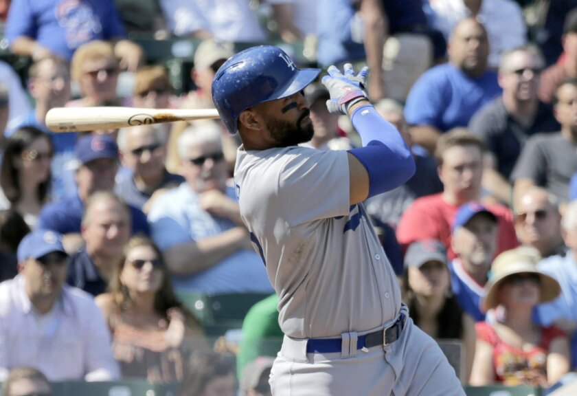 Los Angeles Dodgers' Matt Kemp hits a three-run home run off Chicago Cubs starting pitcher Edwin Jackson, scoring Yasiel Puig and Adrian Gonzalez, during the first inning of a baseball game Friday, Sept. 19, 2014, in Chicago. (AP Photo/Charles Rex Arbogast)