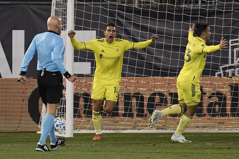 Nashville SC's Daniel Ríos, center, celebrates his overtime goal with teammate Taylor Washington, right, during an MLS soccer playoff match against Toronto FC, Tuesday, Nov. 24, 2020, in East Hartford, Conn. (AP Photo/Jessica Hill)