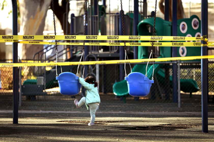 A child plays in a closed playground in Redondo Beach.