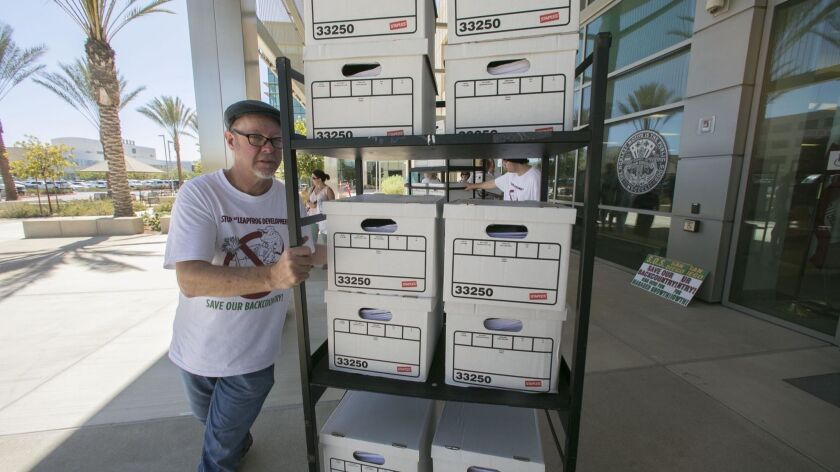 Tim Doring helped wheel boxes of signatures on to a cart to take in to the office of the County Registrar of Voters Monday. The group San Diegans for Managed Growth turned in 107,076 signatures