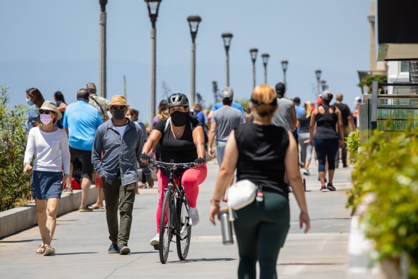 People take advantage of the newly opened walking path on the Strand in Manhattan Beach on Friday.