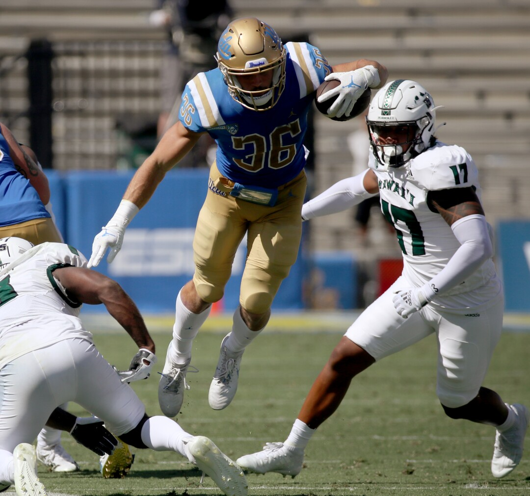 UCLA running back Ethan Femea fights for extra yards against Hawaii in the third quarter.