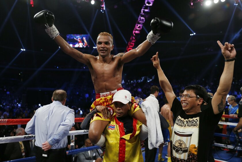 Thailand's Amnat Ruenroeng celebrates after winning the IBF flyweight title belt boxing match against China's double Olympic gold medalist Zou Shiming at the Venetian Macao in Macau, Saturday, March 7, 2015. (AP Photo/Kin Cheung)