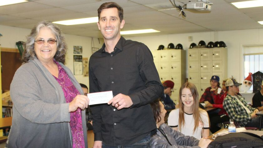 With some of his construction students in the background, Montecito High School teacher Nick Jordan accepts a check for $500 for the school's construction program from Ramona Rotary Club president Kim Lasley.