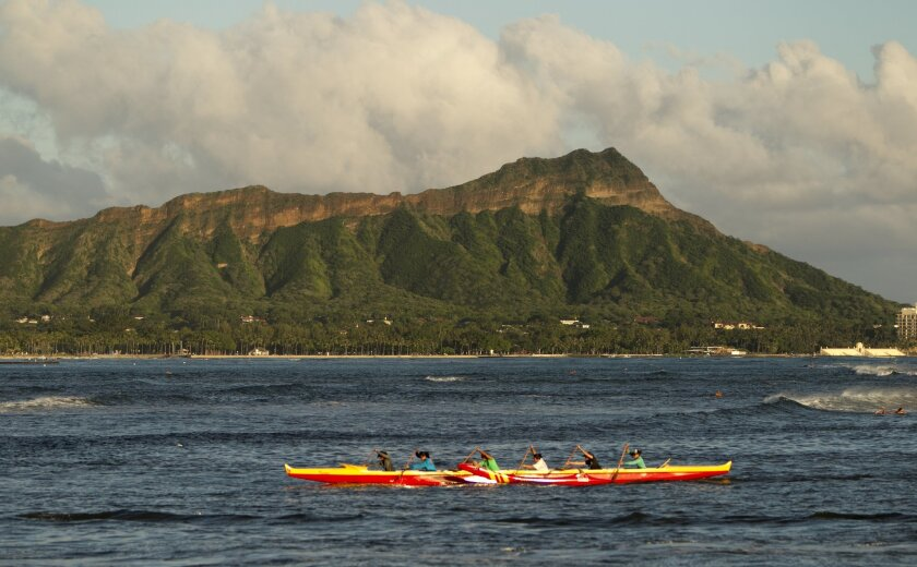 A outrigger canoe paddles past Diamond Head mountain, Wed. Sept. 16, 2015 in Honolulu. A powerful magnitude-8.3 earthquake hit off Chile's northern coast Wednesday night putting Hawaii under a tsunami advisory. Diamond Head is unusually green due to the recent heavy rains. (AP Photo/Marco Garcia)