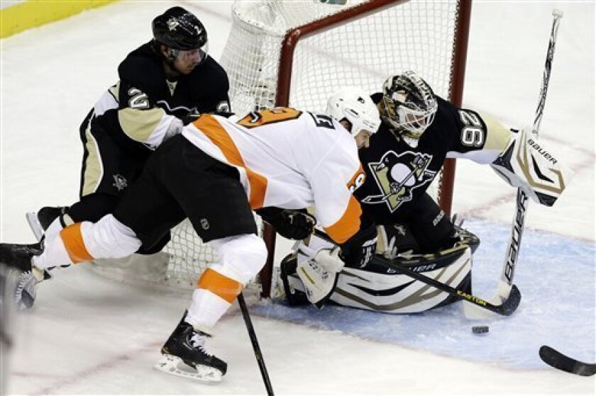 Philadelphia Flyers right wing Mike Knuble (9) cannot get a wraparound shot past Pittsburgh Penguins goalie Tomas Vokoun (92) and defenseman Matt Niskanen (2) in the first period of an NHL hockey game in Pittsburgh, Wednesday, Feb. 20, 2013. (AP Photo/Gene J. Puskar)