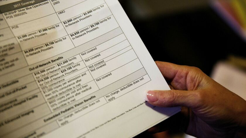 FILE - In this Monday, Dec. 4, 2017, file photo, a woman looks over her health insurance benefit com