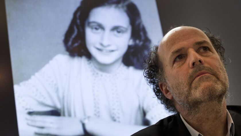 A picture of Anne Frank is projected as director Ronald Leopold of the Anne Frank Foundation listens