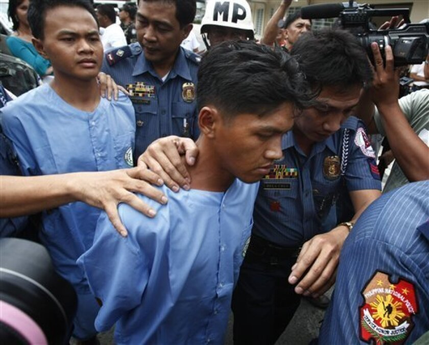 Police and military escort two of three alleged members of the Abdul Basit Usman's terror cell, center and center left in blue, following a news conference Friday, March 5, 2010, at the Armed Forces of the Philippines headquarters at Manila's Quezon city. The three men accused of deadly bombings in the Philippines were arrested Wednesday and bomb parts were seized in a raid that was another blow to the al-Qaida-linked militant group Abu Sayyaf, police said. (AP Photo/Bullit Marquez)