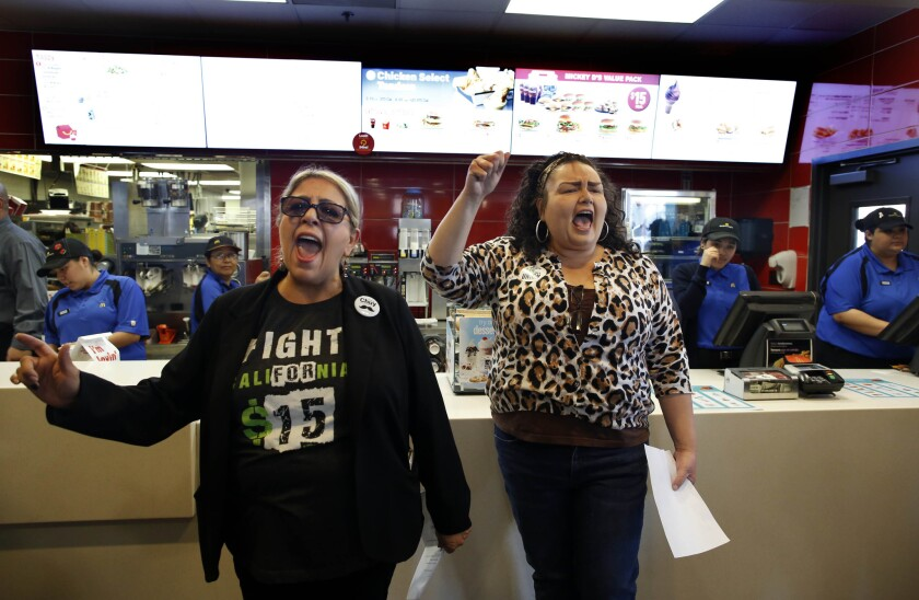 Protesters demonstrate for higher wages inside a McDonald's restaurant in Los Angeles on April 2, following the company's decision to raise minimum wage by $1 an hour at corporate-owned restaurants.