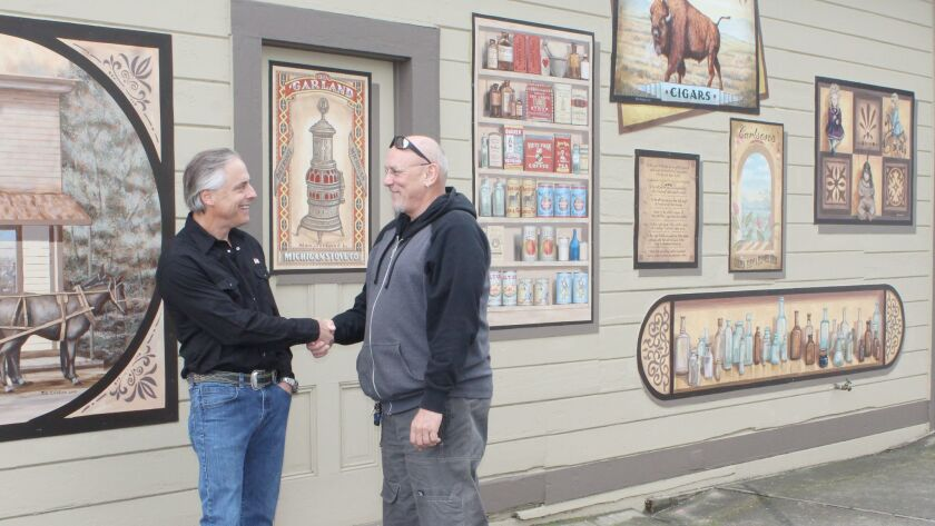 Peter Bidegain, owner of Reds, Whites & Brews, and muralist Rik Erickson shake hands at the ceremony.